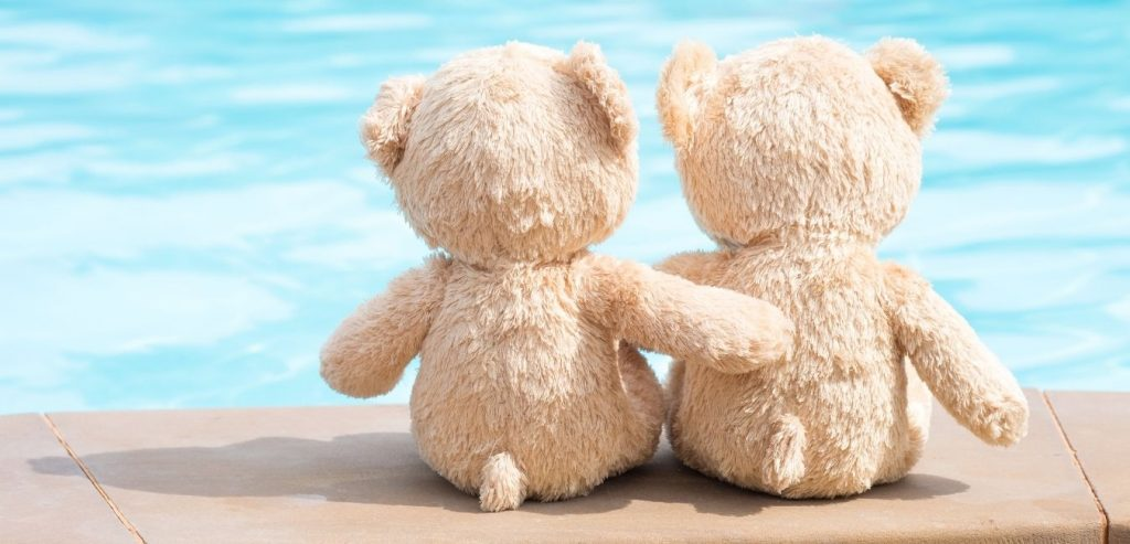 Two teddy bears next to each other overlooking water