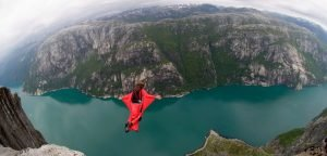 A base jumper in a red jumpsuit launching into a gorge