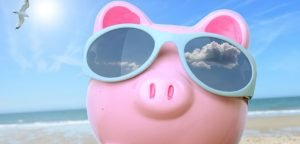 close up of piggy bank wearing sunglasses on the beach